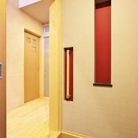 玄関.ホール:朱色の奥壁ニッチと手摺棒。(壁面から沈めて邪魔にならないように納める)