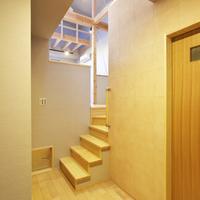 1階吹抜ホールからスキップ2階に上がる階段と手摺棒。壁は吸放湿量が珪藻土の4~5倍で脱臭効果が優れシックハウス対策に有効なエコカラット300ロ貼。