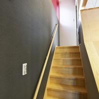 主階段と手摺棒。壁はグレーと朱色の斬新なスタイル。