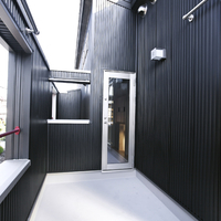 バルコニー:屋外リビング、物干し場として利用。FRP防水床、目隠しの為の高い手摺、朱色の手摺パイプと黒色メタルサイディングを見る。