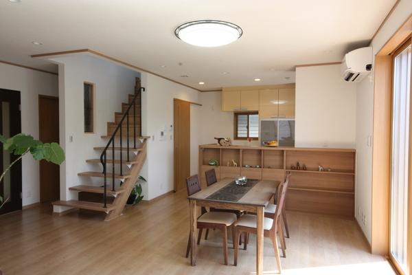 茶の間より見るリビングダイニング、キッチン・対面キッチンの背面を利用し収納棚を、アイアン手摺のオープンな階段