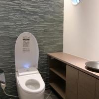 丸い小窓が可愛い素敵な石貼りのトイレ