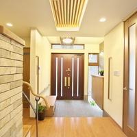 玄関ホール、天井木製格子と白い玉石、ボーダータイルが内外部を繋ぐ